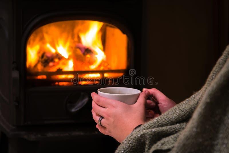 Femme ayant une tasse chaude de piste à la cheminée Firepla brûlant photos stock