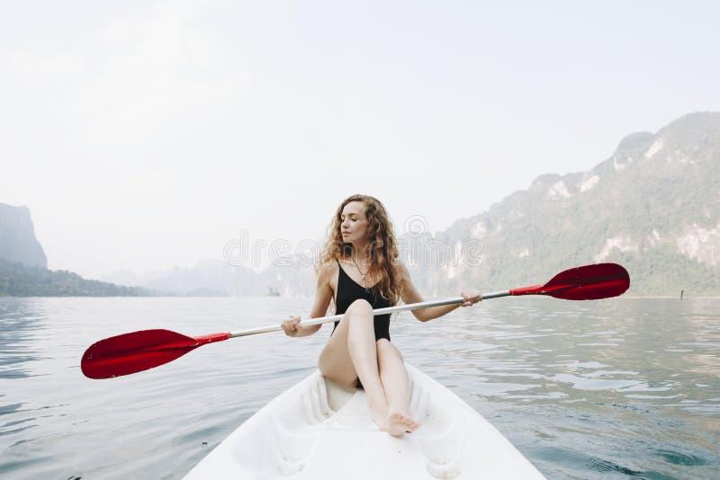 Femme barbotant un canoë par un parc national images stock