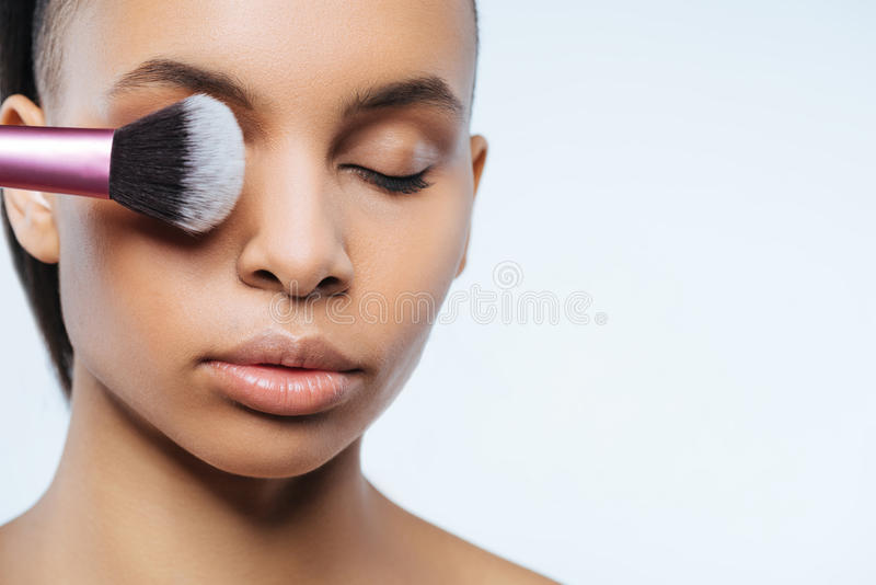 Femme belle attirante mettant sur le maquillage photo stock