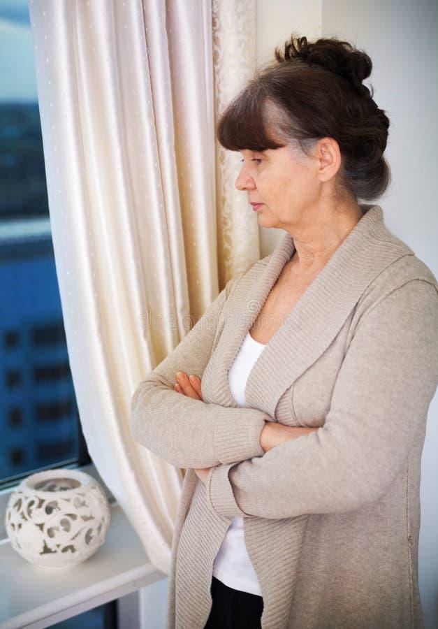 Femme belle d'âge d'admission à la pension à côté de fenêtre images stock