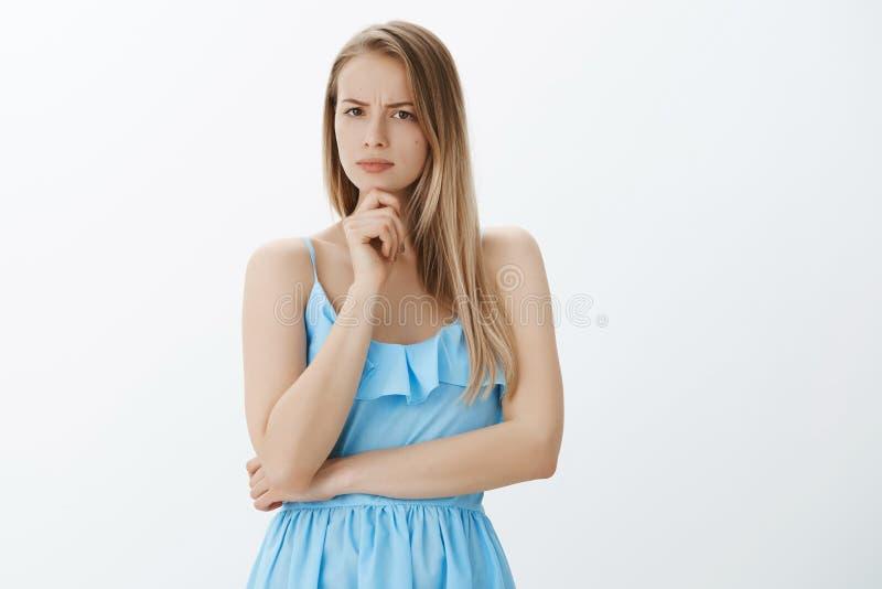 femme belle perturbée et méfiante à l'air sérieux dans la robe bleue avec les cheveux justes fronçant les sourcils tenant la main photo libre de droits
