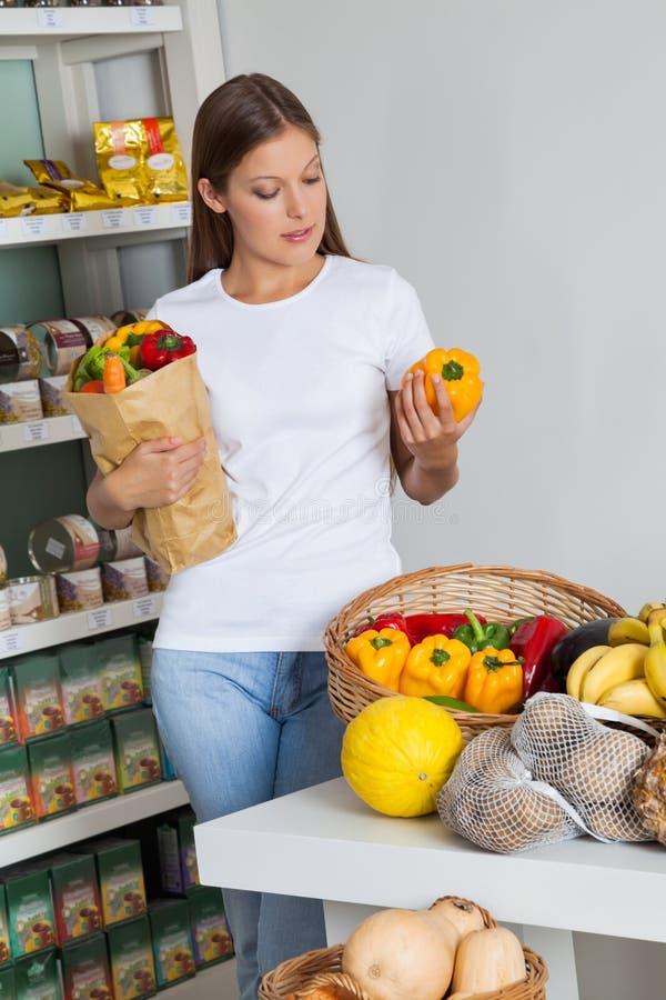Femme Bellpeppers de achat dans le supermarché photo stock