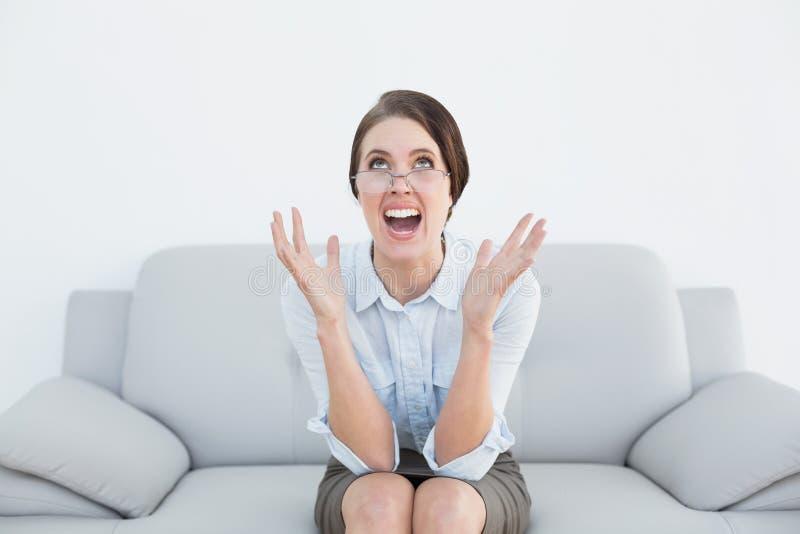 Femme bien habillée contrariée criant sur le sofa photos libres de droits