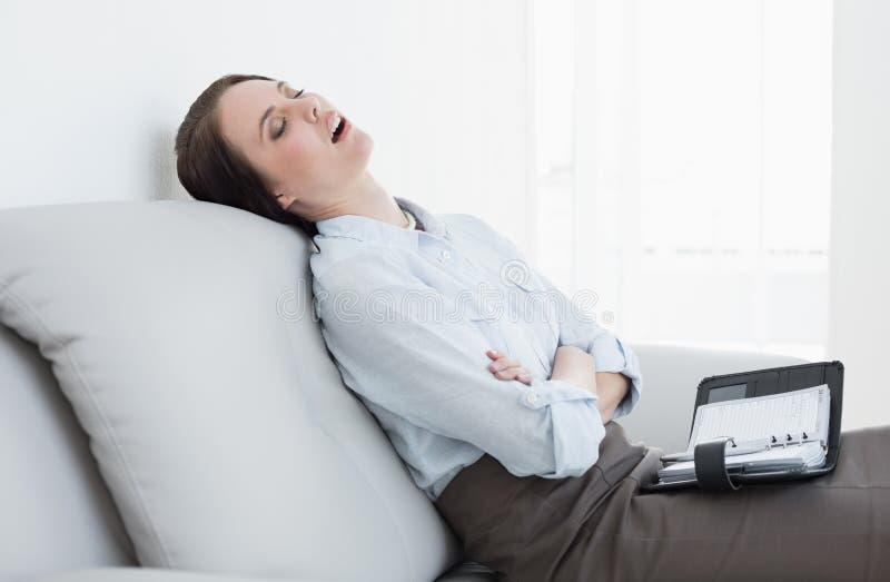 Femme bien habillée s'asseyant et dormant sur le sofa photos stock