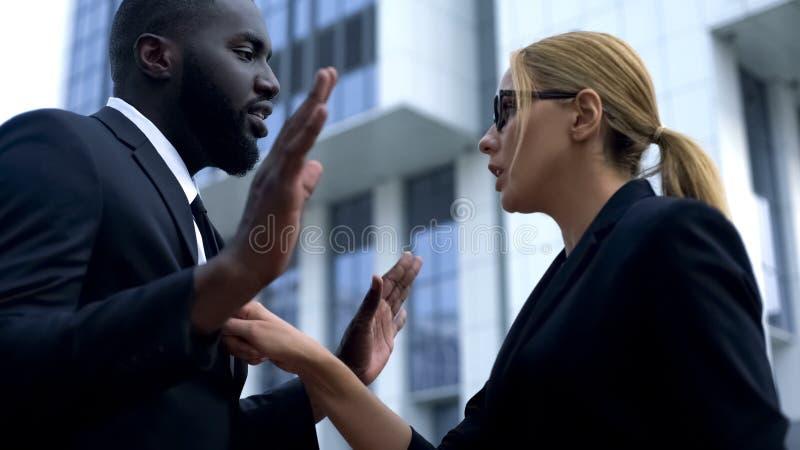 Femme blâmant l'employé afro-américain dans l'échec de démarrage, discrimination raciale photos libres de droits
