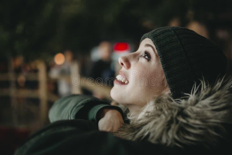 Femme blanche de sourire portant un chapeau et un manteau verts de knit, recherchant et observant des lumières de ville au cours  image libre de droits