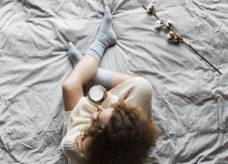 Femme blanche s'asseyant sur le lit avec du lait chaud en hiver photo stock