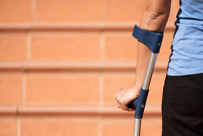 Femme blessée essayant de marcher sur des béquilles photographie stock libre de droits