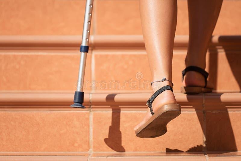 Femme blessée essayant de marcher sur des béquilles image libre de droits
