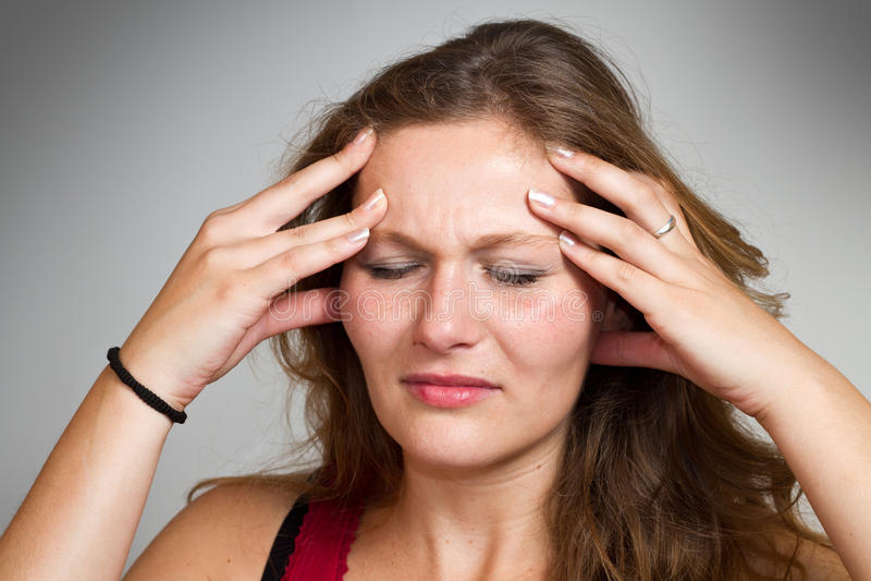 Femme blond ayant un mal de tête photographie stock