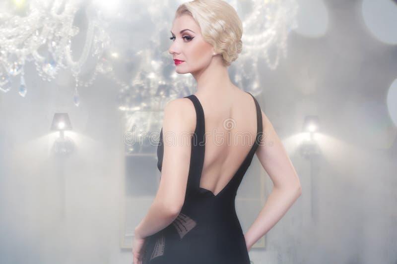 Femme blond dans la robe noire à l'intérieur images libres de droits