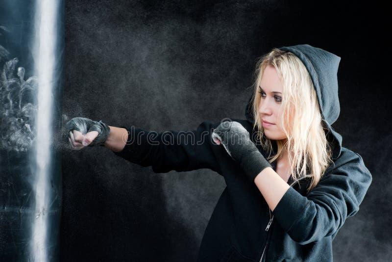 Femme blond de boxe dans le sac de poinçon noir photo stock