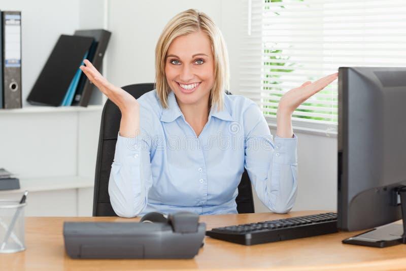 Femme blond de sourire s'asseyant derrière le bureau photos stock