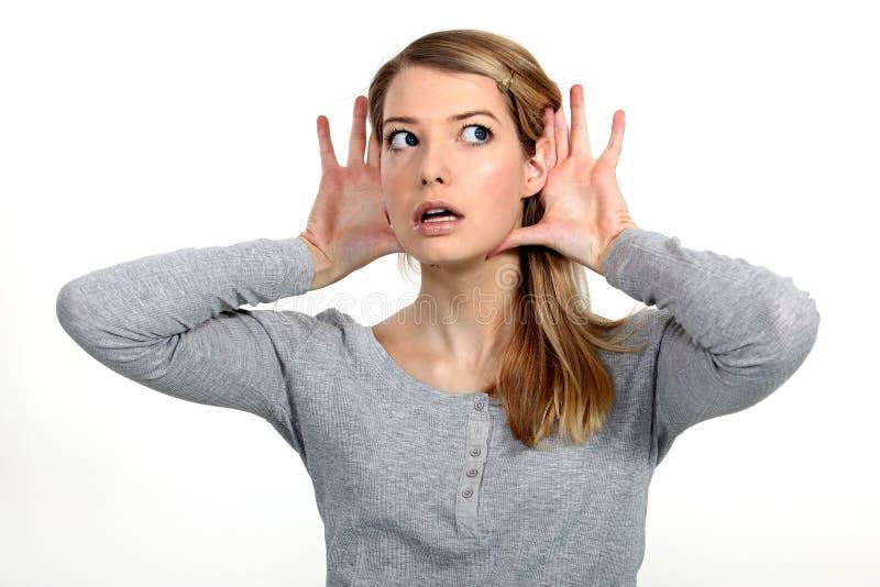 Femme blond luttant pour entendre photos stock