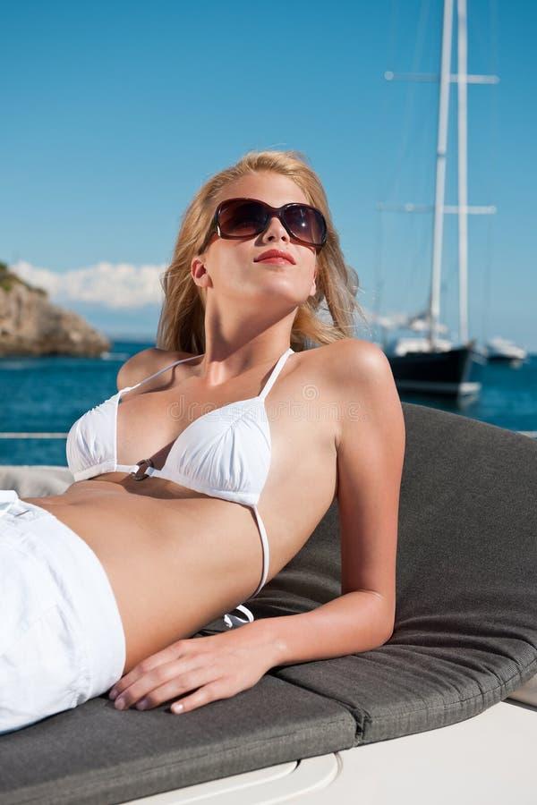 Femme blond s'exposant au soleil sur le yacht de luxe avec le bikini image libre de droits