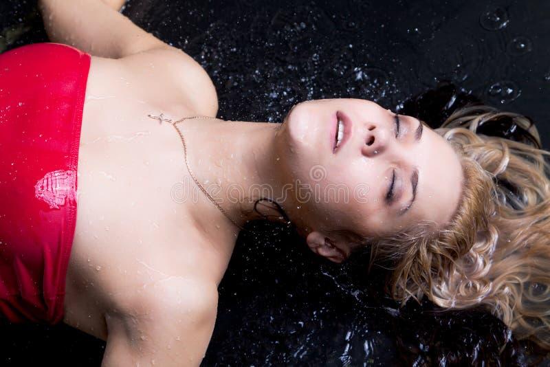 Femme blond se situant dans l'eau image stock