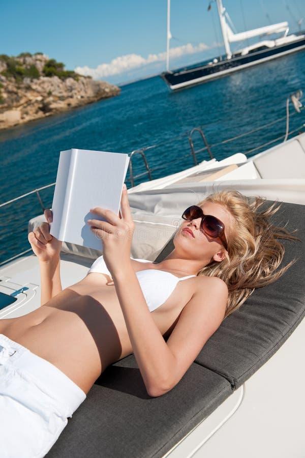 Femme blond se trouvant sur le livre de relevé de yacht image stock
