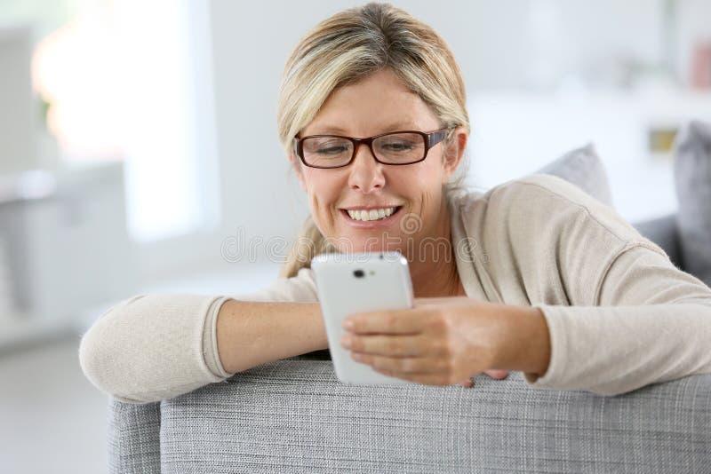 Femme blonde à la mode à l'aide du smartphone photos libres de droits
