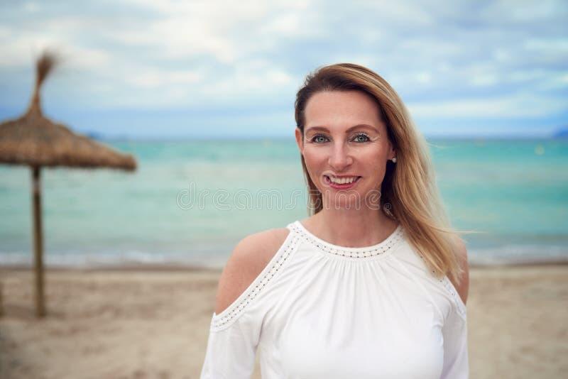 Femme blonde à la mode attirante dans un dessus élégant se tenant sur une plage tropicale de station de vacances photographie stock libre de droits