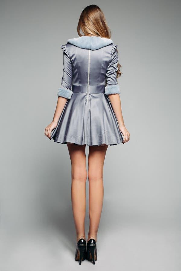 Femme blonde à la mode avec de longues jambes utilisant le costume gris avec le collier et les douilles de fourrure images libres de droits