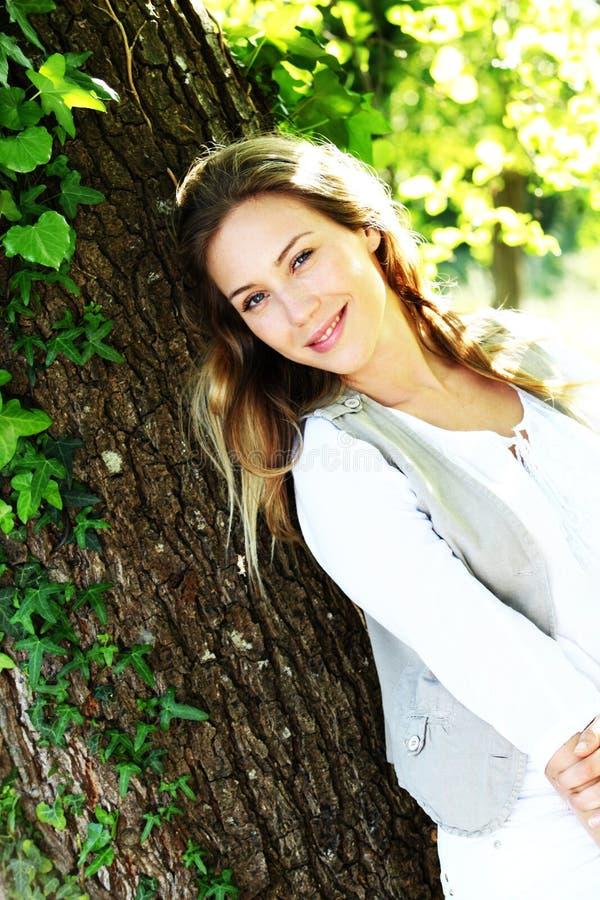 Femme blonde à la mode de sourire se penchant sur l'arbre image libre de droits