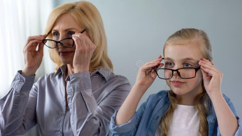 Femme blonde âgée et sa petite-fille mettant sur des lunettes et souriant, santé photo libre de droits