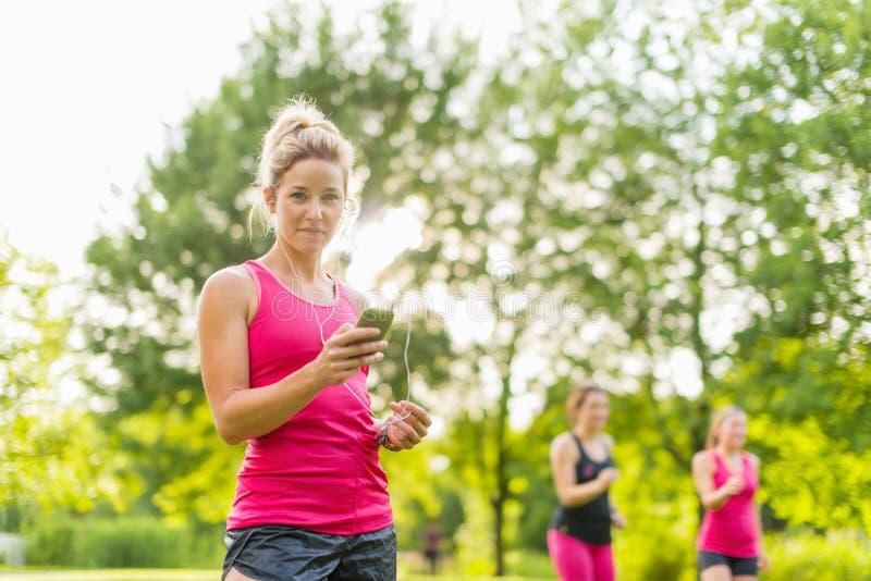 Femme blonde écoutant la musique pendant le sport photos libres de droits