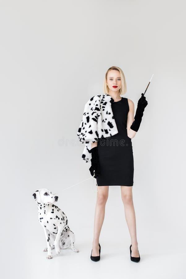 femme blonde élégante attirante chez le chien dalmatien de robe de cigarette noire de participation photo stock