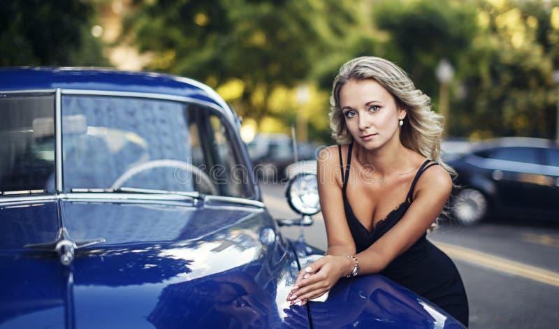 Femme blonde élégante avec la voiture bleue de vintage images stock