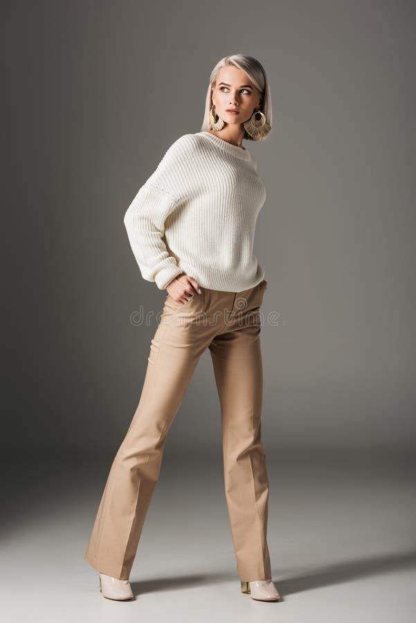 femme blonde élégante posant dans le chandail blanc et le pantalon beige photo libre de droits