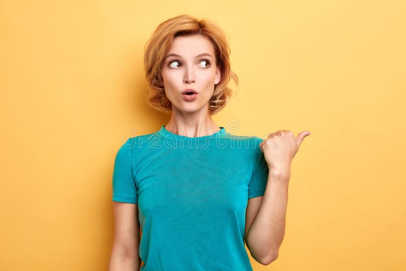 Femme blonde émotive stupéfaite indiquant le côté photographie stock libre de droits