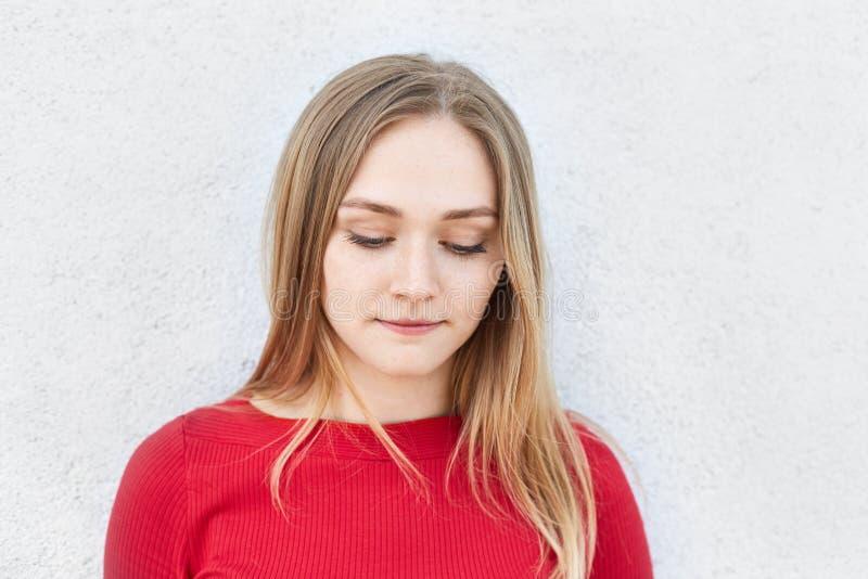 Femme blonde adorable dans la robe rouge regardant pensivement en bas de la pensée au-dessus de ses relations avec l'ami ayant l' images stock