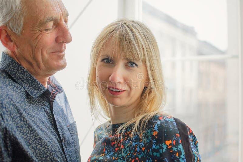 Femme blonde attirante étreignant l'homme supérieur bel et regardant la caméra avec l'amour et passion Ajouter ? l'?ge images libres de droits