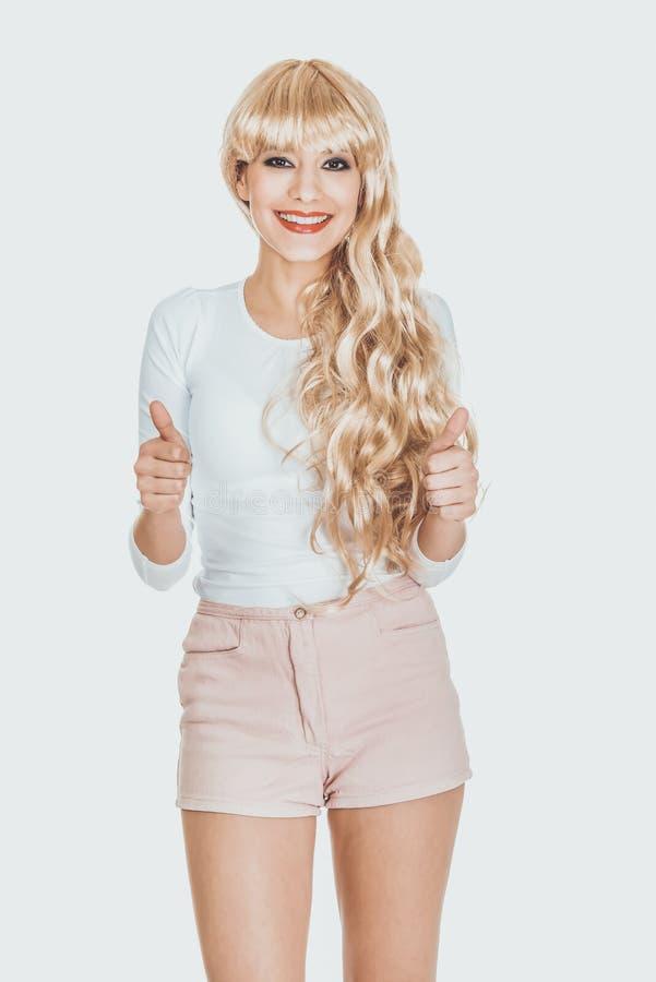 Femme blonde attirante avec des pouces  photos stock