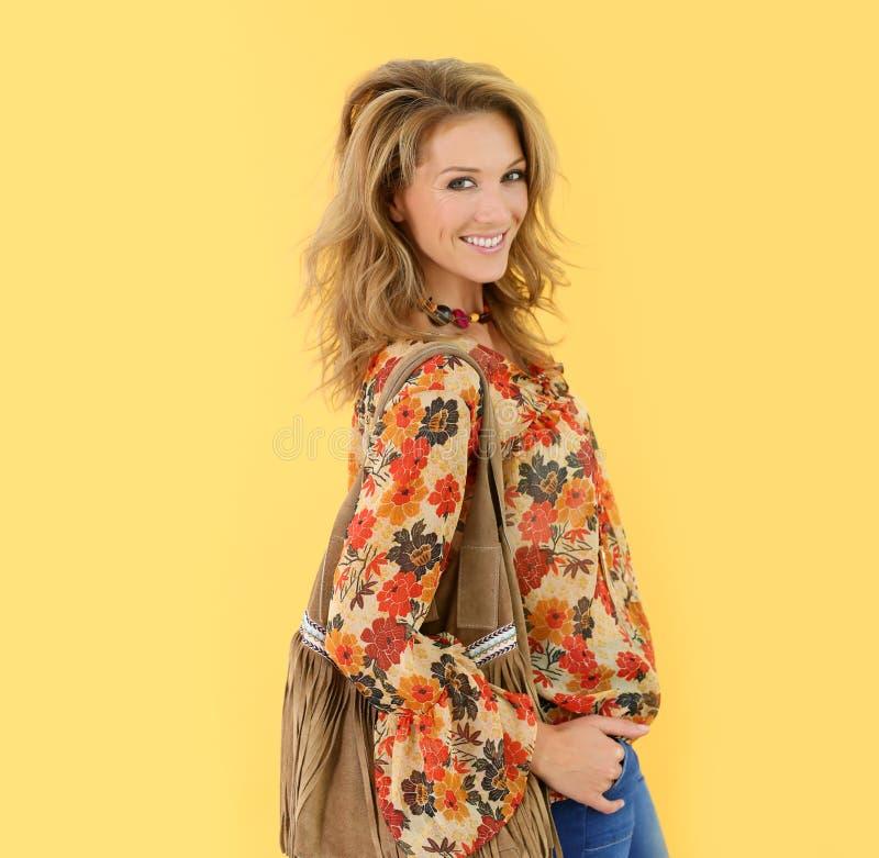 Femme blonde attirante avec le sac en cuir et le sourire à la mode de vêtements images stock