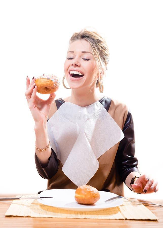 Femme blonde attirante avec une serviette sur son coffre souriant et mangeant le beignet et le sourire heureux d'isolement sur le  images stock