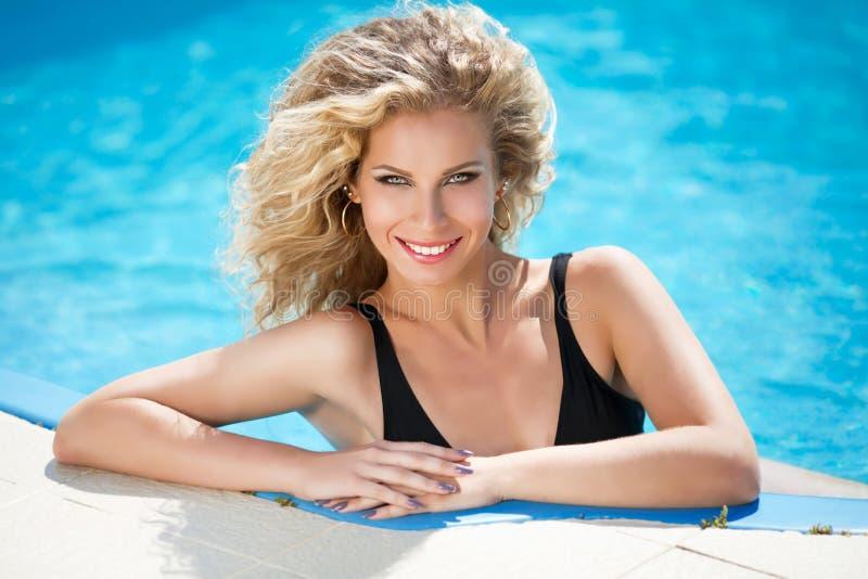 Femme blonde attirante de sourire heureuse dans la piscine de l'eau bleue photo libre de droits