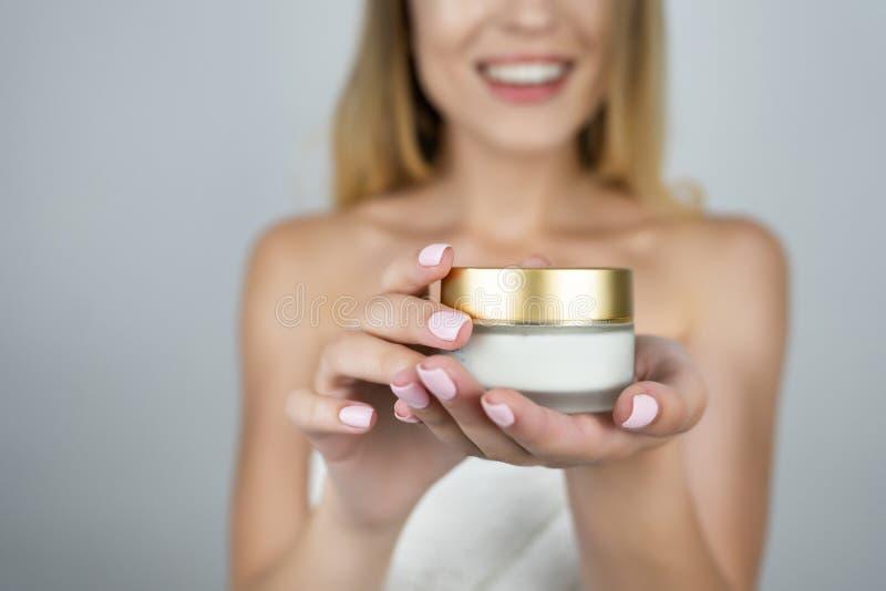 Femme blonde attirante de sourire tenant la crème de beauté dans des ses mains étroites vers le haut du fond blanc d'isolement photographie stock libre de droits