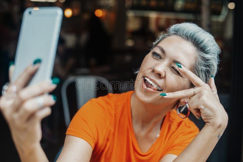 Femme blonde attirante faisant le selfie au café et montrant le signe de la victoire photo stock