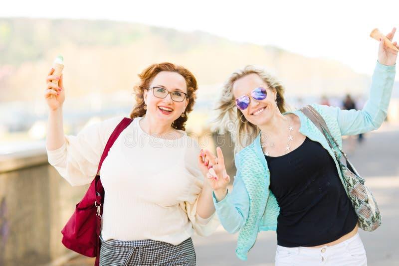 Femme blonde attirante la marche en verre de soleil du centre et en mangeant la crème glacée - femmes insouciantes photos stock