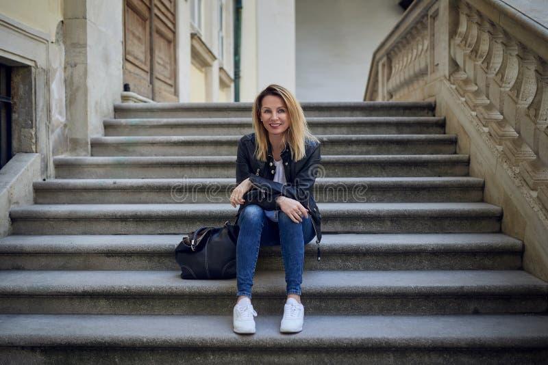 Femme blonde attirante s'asseyant sur les étapes en pierre photo libre de droits