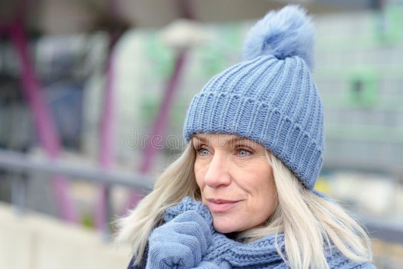 Femme blonde attirante se blottissant dans une écharpe chaude images stock
