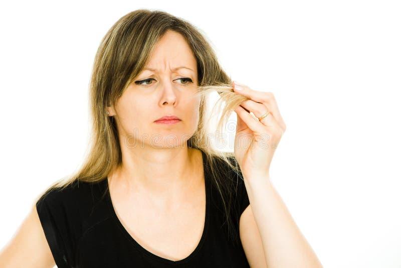 Femme blonde - femme au foyer - voir le probl?me avec de longs poils droits photographie stock libre de droits