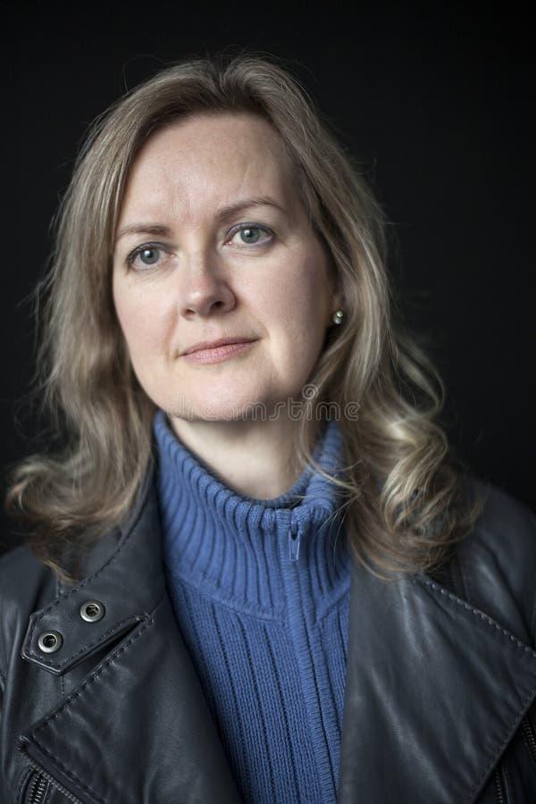 Femme blonde avec de beaux yeux bleus sur le fond noir image stock