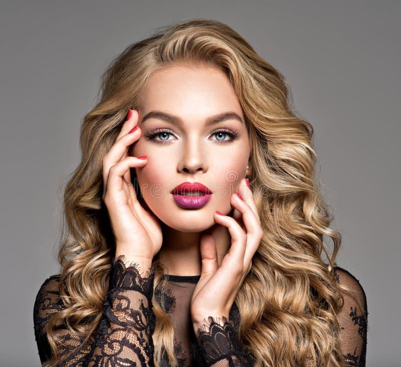 Femme blonde avec de longs beaux cheveux bouclés Maquillage La mode font photographie stock