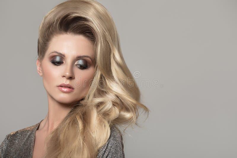 Femme blonde avec de longs beaux cheveux boucl?s Robe grise de scintillement images stock