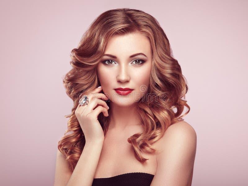 Femme blonde avec de longs cheveux onduleux brillants photographie stock libre de droits