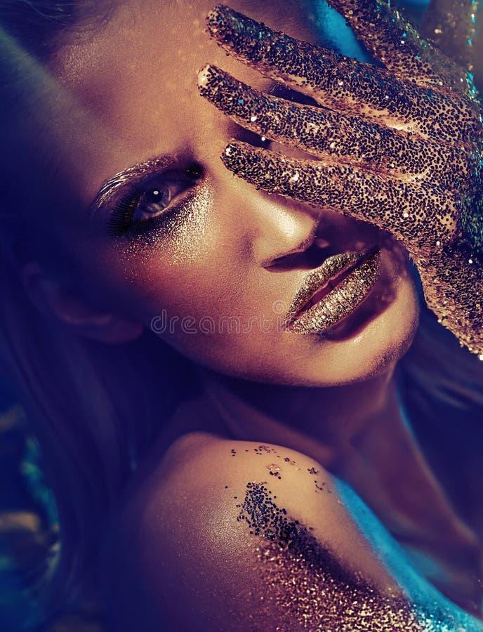 Femme blonde avec de petites pièces en or sur sa peau photo stock