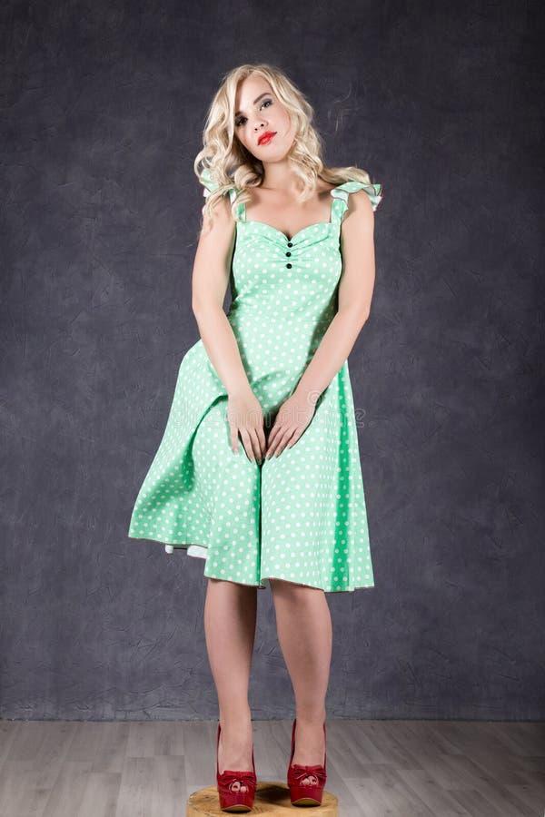 Femme blonde avec des cheveux dans le vent fille sexy avec des cheveux de vol posant dans la robe verte et des chaussures rouges photos stock