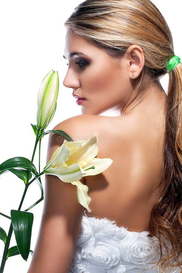 Femme blonde avec la fleur propre fraîche de lis de peau et blanc d'isolement photos libres de droits